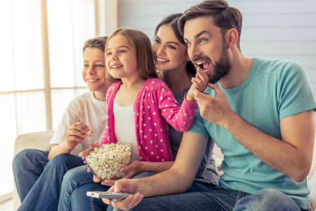 madre e hija adolescente: Beautiful young parents, their  daughter and son are watching TV, eating popcorn and smiling, sitting on sofa at home. Dad is using a remote control