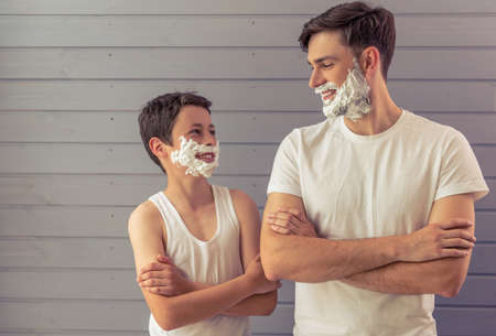 Handsome young father and his teenage son with shaving foam on their faces are looking each other and smiling, standing cross-armed against gray wall 写真素材