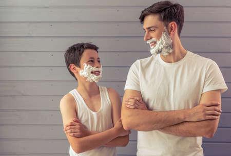 잘 생긴 젊은 아버지와 서로를 찾고 자신의 얼굴에 면도 거품과 미소, 서 그의 십대 아들 회색 벽에 십자가는 무장
