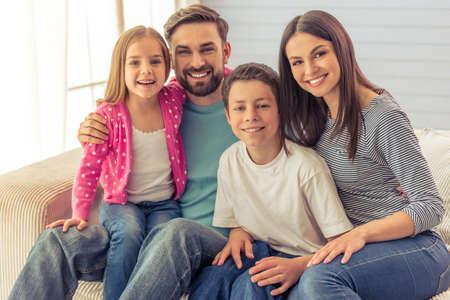 Schöne junge Eltern, ihre nette kleine Tochter und Sohn betrachten Kamera und Lächeln und sitzen auf Sofa zu Hause