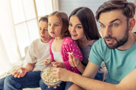 face to face: Beautiful young parents, their  daughter and son are watching TV, eating popcorn and showing surprise, sitting on sofa at home Stock Photo