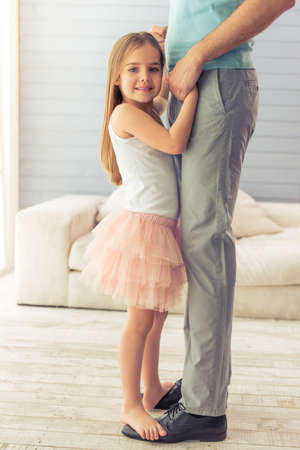 suit skirt: Cropped image of young father and his cute little daughter dancing at home. Girl is standing on her fathers feet, looking at camera and smiling