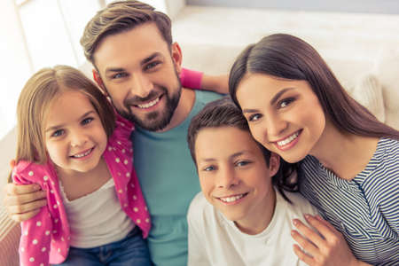 beautiful boy: Portrait of beautiful young parents, their cute little daughter and son looking at camera and smiling, sitting on sofa at home Stock Photo