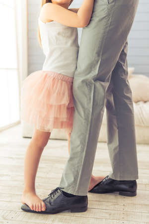 suit skirt: Cropped image of young father and his cute little daughter dancing at home. Girl is standing on her fathers feet Stock Photo