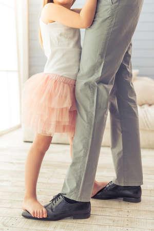 Geerntetes Bild der jungen Vater und seine süße kleine Tochter tanzen zu Hause. Mädchen steht auf Füßen ihres Vaters Standard-Bild
