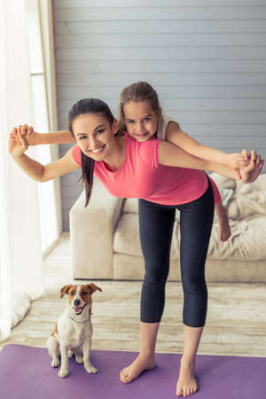 mum and daughter: Beautiful young mother and her cute little daughter are looking at camera and smiling while doing yoga at home, their dog is near Stock Photo