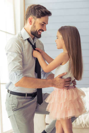 Cute little daughter is adjusting her father's tie. Both are smiling, standing in the room