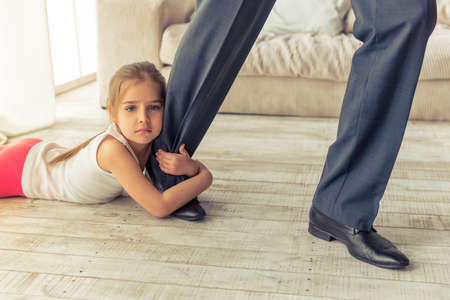 Cropped image of cute little girl looking at camera while hugging her fathers leg not letting him go