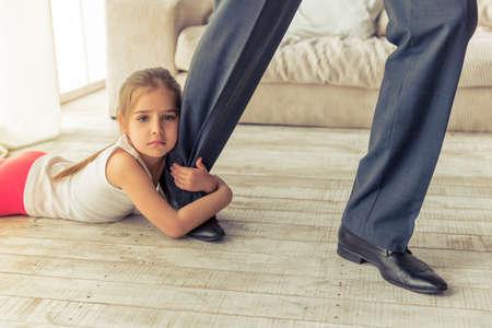 Geerntetes Bild des niedlichen kleinen Mädchen in die Kamera schaut, während ihr Vater umarmt Bein ließ ihn nicht gehen