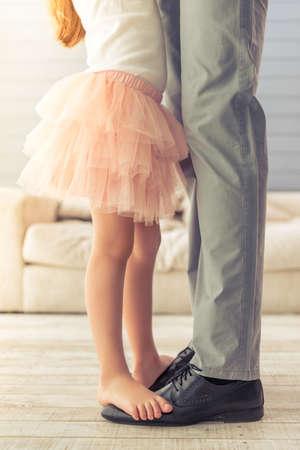 젊은 아버지와 집에서 춤을 그의 귀여운 작은 딸의 자른 된 이미지. 소녀는 아버지의 발 앞에 서 있습니다.