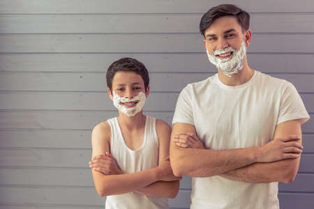 Handsome young father and his teenage son with shaving foam on their faces are looking at camera and smiling, standing cross-armed against gray wall Stock Photo