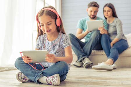 mum and daughter: Cute little girl in headphones is using a tablet and smiling, in the background her parents are using a tablet too, sitting on sofa at home