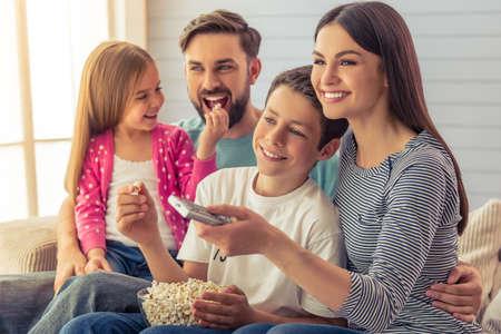 美しい若い親とその娘と息子がテレビを見て、ポップコーンを食べて、笑って、家でソファーに座っていた。Mom は、リモート制御を使用します。