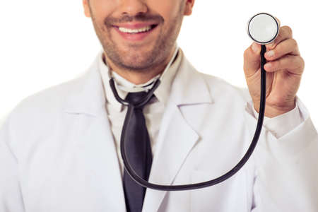 oncologist: Cropped image of handsome doctor in white coat smiling while holding a stethoscope, isolated on white background