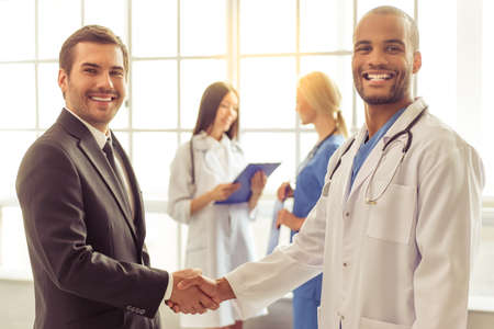 Handsome businessman and Afro American doctor are shaking their hands, looking at camera and smiling, two female doctors are talking in the background