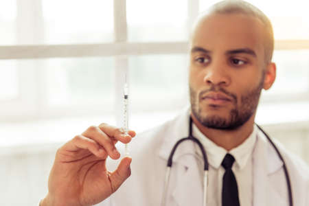 oncologist: Handsome Afro American doctor in white coat is holding a syringe and looking at it. Hand with syringe in focus