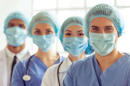 Los médicos de diferentes nacionalidades y géneros en las máscaras y las tapas están mirando a la cámara, de pie en una fila uno por uno Foto de archivo