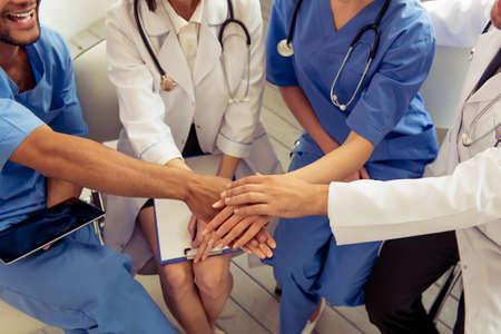 Imagen recortada de médicos de diferentes nacionalidades y géneros que llevan a cabo las manos juntas y sonriendo, sentado en la oficina