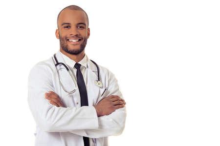 Portret van knappe Afro-Amerikaanse arts in witte jas kijken camera en glimlachen terwijl je met gekruiste armen, geïsoleerd op een witte achtergrond Stockfoto