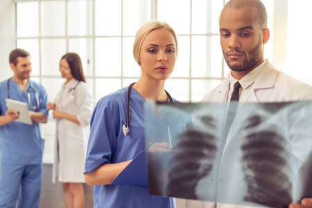 oncologist: Beautiful female and handsome Afro American doctors are examining X-ray photograph, two other doctor are talking in the background Stock Photo