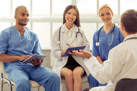 nationalities: Medical doctors of different nationalities and genders are making notes, talking and smiling, sitting in office