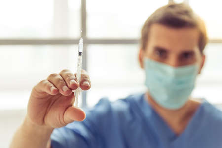 reliever: Handsome doctor in blue medical wear and mask is holding a syringe and looking at camera. Hand with syringe in focus Stock Photo