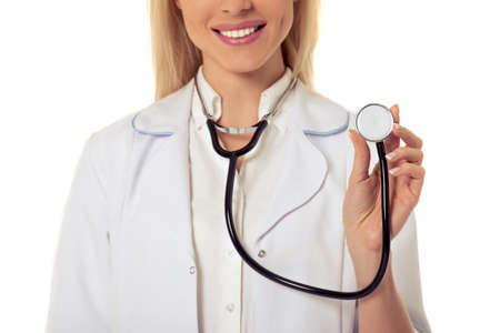 oncologist: Cropped image of beautiful female doctor in white coat smiling while holding a stethoscope, isolated on white background
