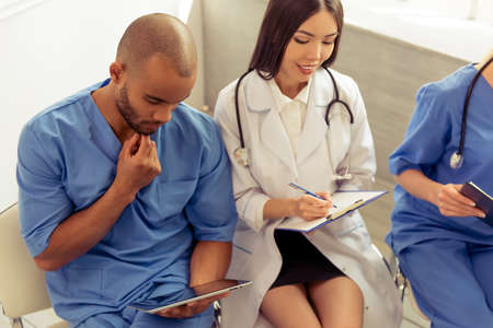 oncologist: Medical doctors of different nationalities and genders with folders and tablet are doing their staff and smiling, sitting in office