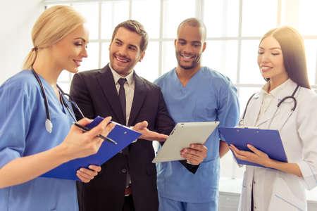 古典的なスーツでハンサムな実業家はタブレットを使用して、フォルダー、オフィスで立っていると医師に話しています。すべてが笑っています。 写真素材