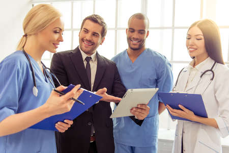 Handsome businessman in classic suit is using a tablet and talking to medical doctors with folders, standing in office. All are smiling