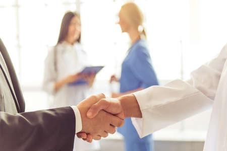 実業家とアフロ アメリカ人医師に手を振ってのトリミングされた画像は、2 人の女性医師は、バック グラウンドで話しています。
