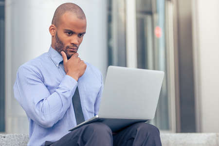 american banker: Handsome young pensive Afro American businessman in classic clothes is using a laptop and thinking while working outdoors