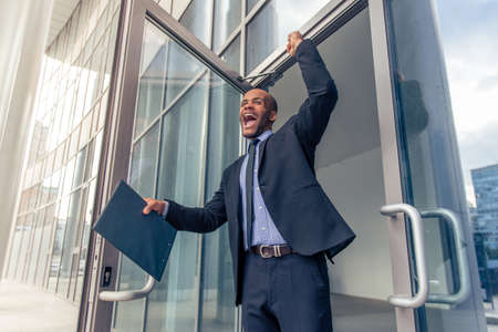 american banker: Low angle view of handsome young Afro American businessman in classic suit holding folder, keeping fist up and screaming with happiness while leaving office building