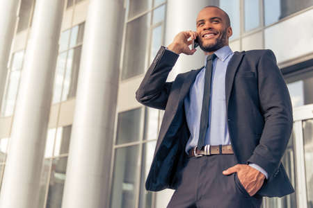 american banker: Handsome young Afro American businessman in classic suit talking on the mobile phone and smiling, standing outdoors near the office building Stock Photo