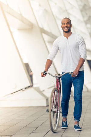 Handsome young Afro American man in casual clothes is smiling while walking with bike outdoors