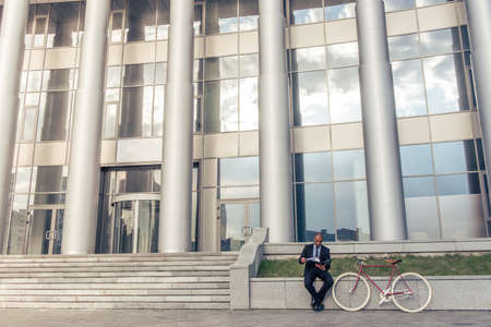 american banker: Panorama view of office building, handsome Afro American businessman in classic suit is examining documents, sitting near his bike