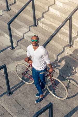High angle view of handsome young Afro American man in casual wear and sun glasses leaning on his bike while standing on stairs outdoors Stock Photo