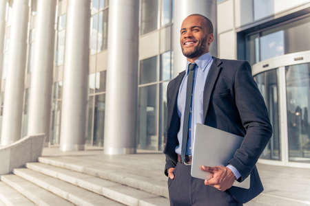 古典的なスーツ ラップトップを押しながら笑みを浮かべて、屋外で立って事務所ビルの近くでハンサムな若いアフロ アメリカのビジネスマン