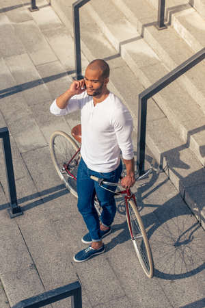 High angle view of handsome young Afro American man in casual wear talking on mobile phone and leaning on his bike while standing on stairs outdoors