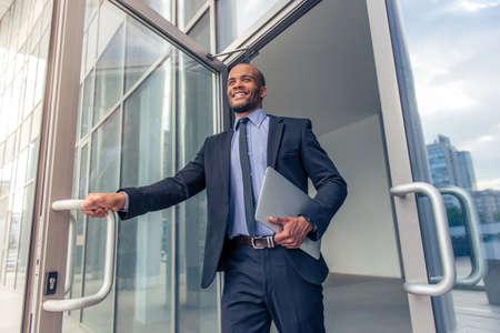 ángulo de visión baja de apuesto joven empresario afroamericano en traje clásico con un ordenador portátil y una sonrisa, dejando el edificio de oficinas