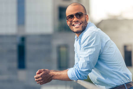 Handsome young Afro American businessman in sun glasses is looking at camera and smiling while leaning on balcony balustrade outdoors Stock Photo