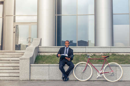 american banker: Handsome Afro American businessman in classic suit is examining documents, looking at camera and smiling while sitting outside the office building near his bike