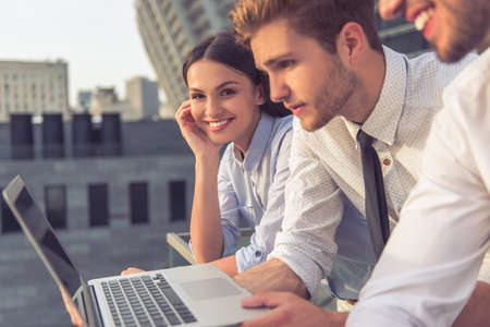 Handsome young businessmen and lady in classic clothes are using a laptop and smiling, standing on balcony of the office building. Girl is looking at camera
