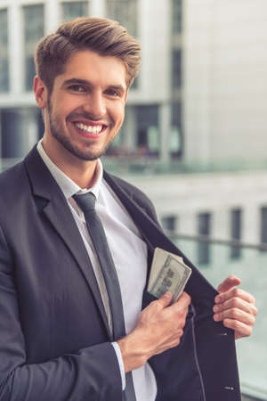 putting money in pocket: Handsome young businessman in classic suit is putting money into the inner pocket of his jacket, looking at camera and smiling, standing near the office