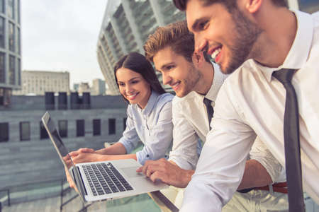 Side view of handsome young businessmen and lady in classic clothes using a laptop and smiling, standing on balcony of the office building