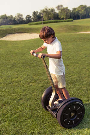 Cute little boy in casual clothes is smiling while riding a segway in the park
