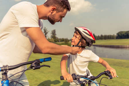 fastening: Handsome young dad and his cute little son in casual clothes are riding bikes in park. Father is fastening his sons helmet