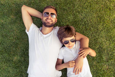 Top view of cute little boy and his handsome young dad in white T-shirts and sun glasses smiling while on the grass