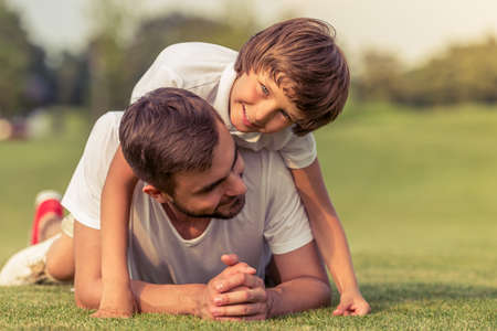 Cute little boy and his handsome young dad are smiling while lying on the grass in the park. Son is pickaback Stock Photo