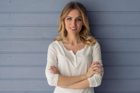 Beautiful young woman is looking at camera and smiling, standing with crossed arms against gray wall